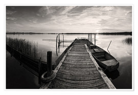 Premiumposter  Wooden pier on lake with fishing boat - black and white - Frank Herrmann