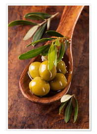 Premiumposter Spoon with green olives on a wooden table